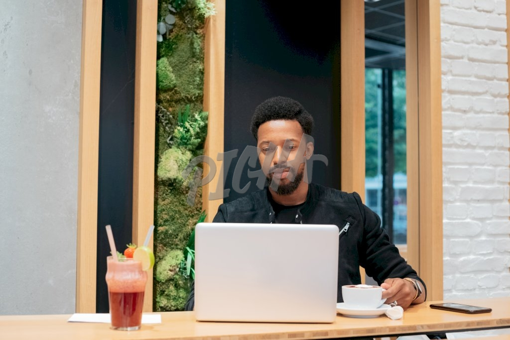 young stylish man works on his laptop while at a coffee shop