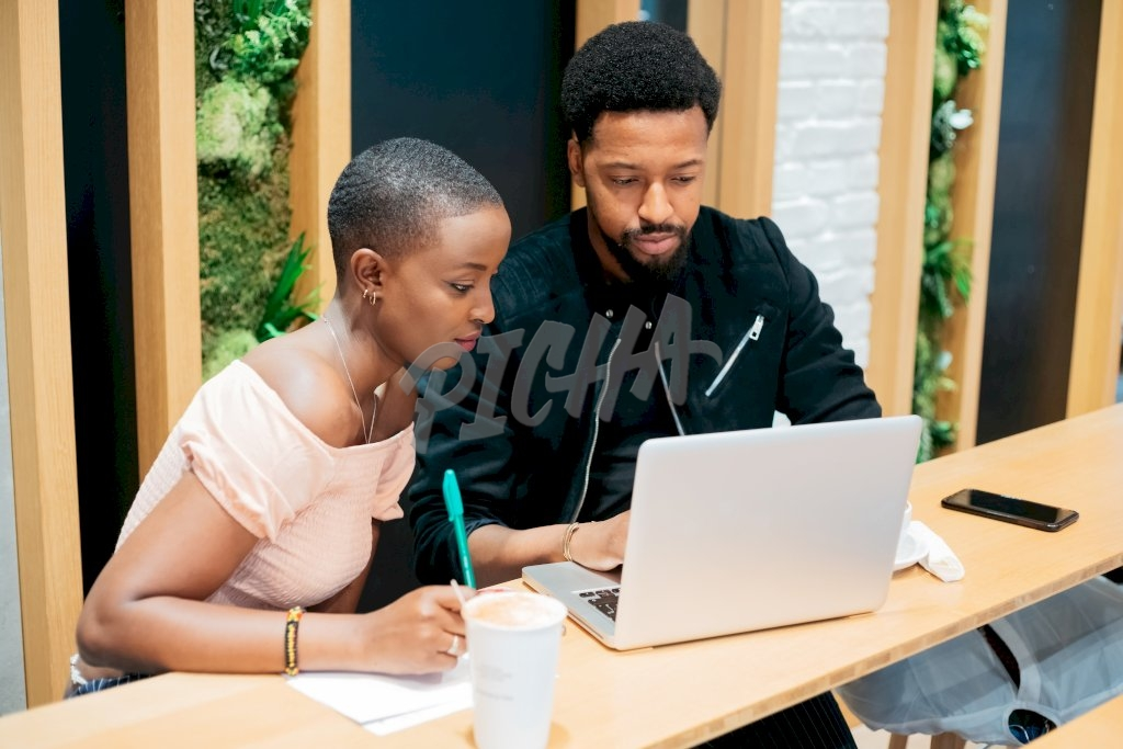 Young man and woman working together using a laptop and a notepad