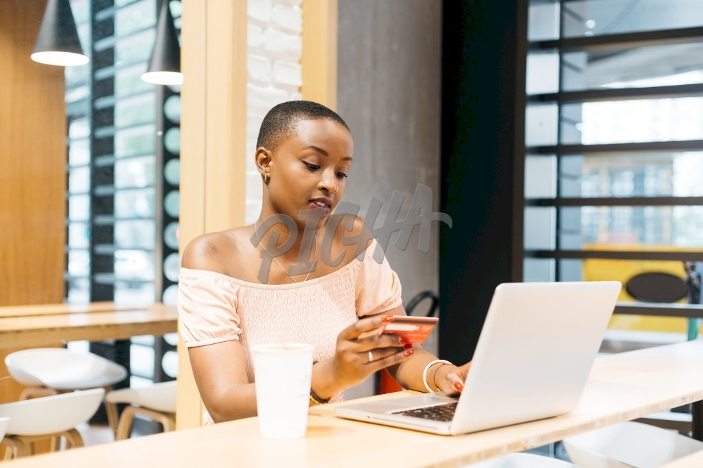 lady makes an online payment from her laptop while seated at a coffee shop