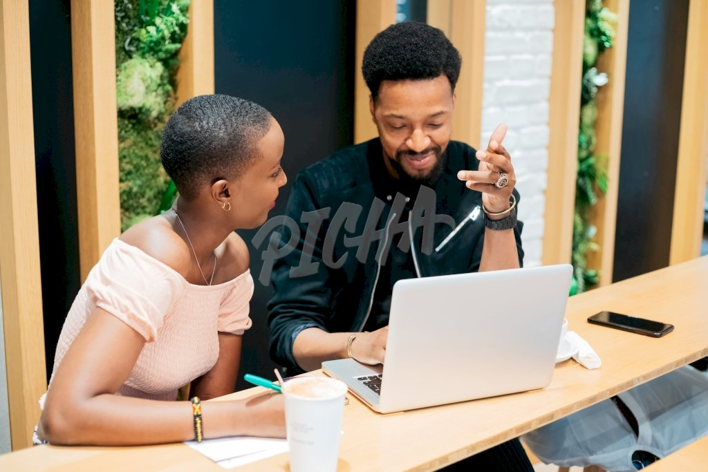 couple have a discussion while using a laptop