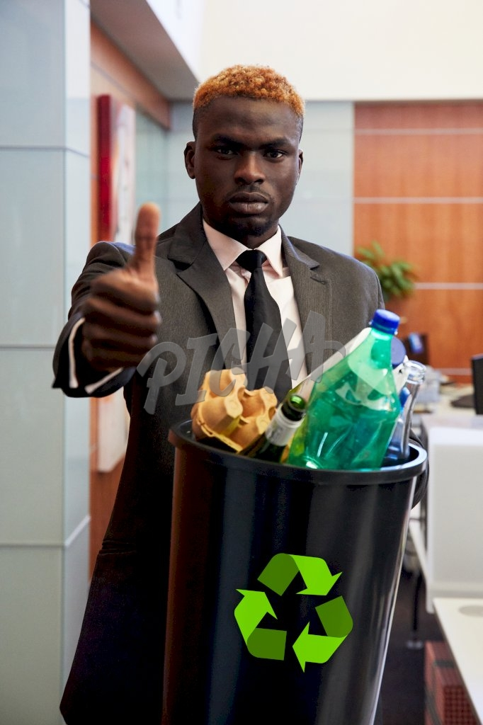 Man shows a thumbs up while holding onto a waste bin in the office