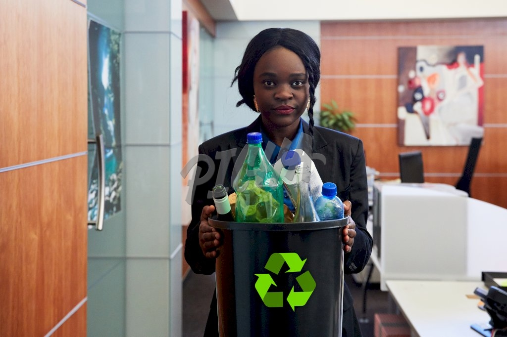 lady holds onto a waste bin while standing in an office aisle
