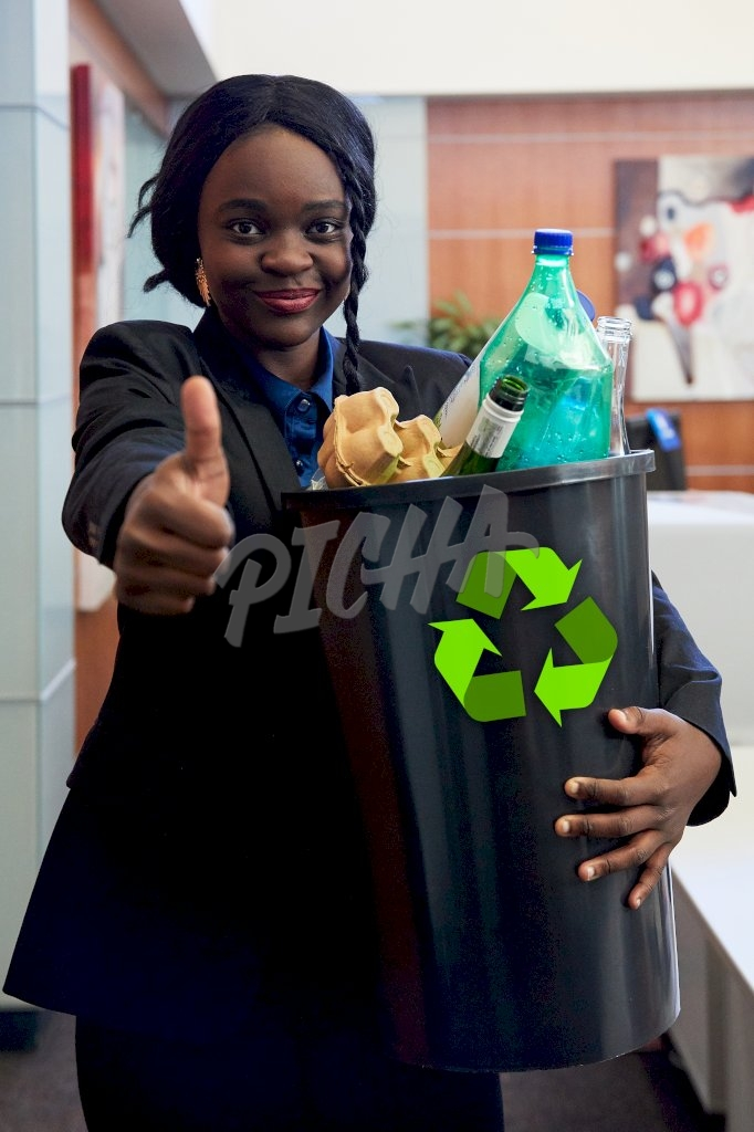 lady shows a thumbs up while holding onto a waste bin in the office