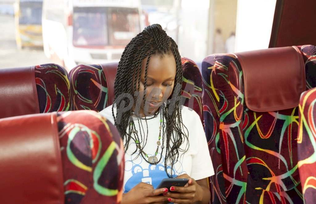 Young woman on the bus checking phone