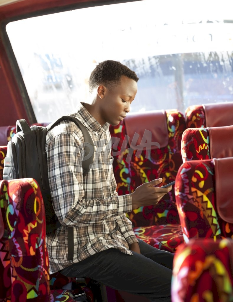 Young man sitting on the bus checking phone