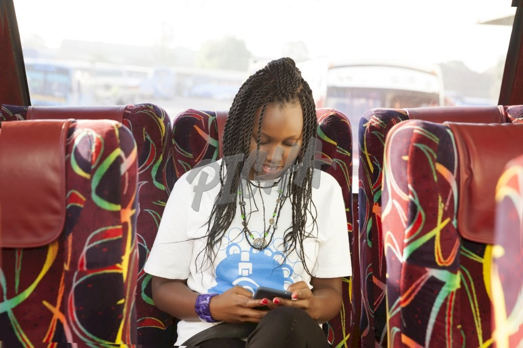 Woman sitting on the bus checking phone