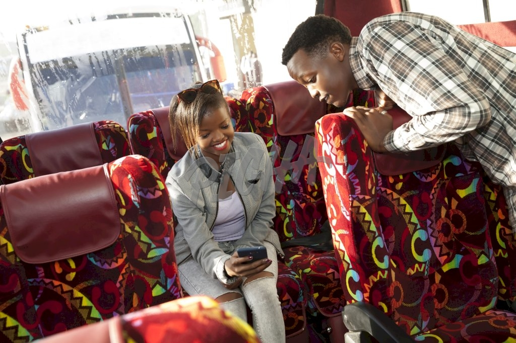 Young man and young girl checking phone while on the bus