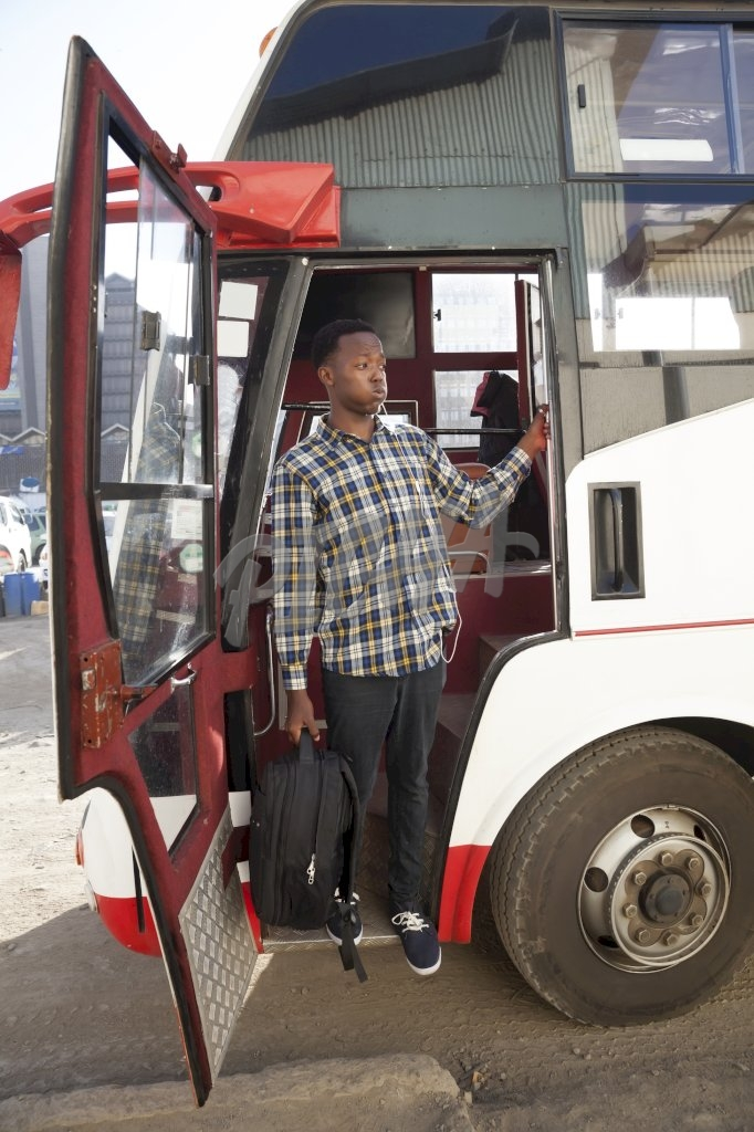 Young man getting off the bus