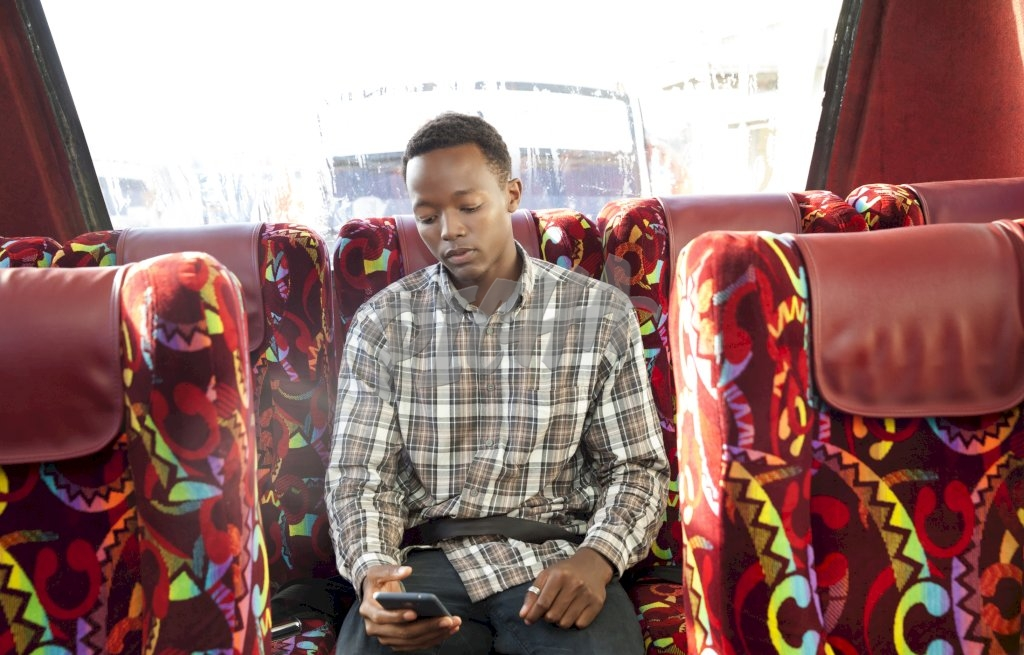 Young man checking phone on the bus
