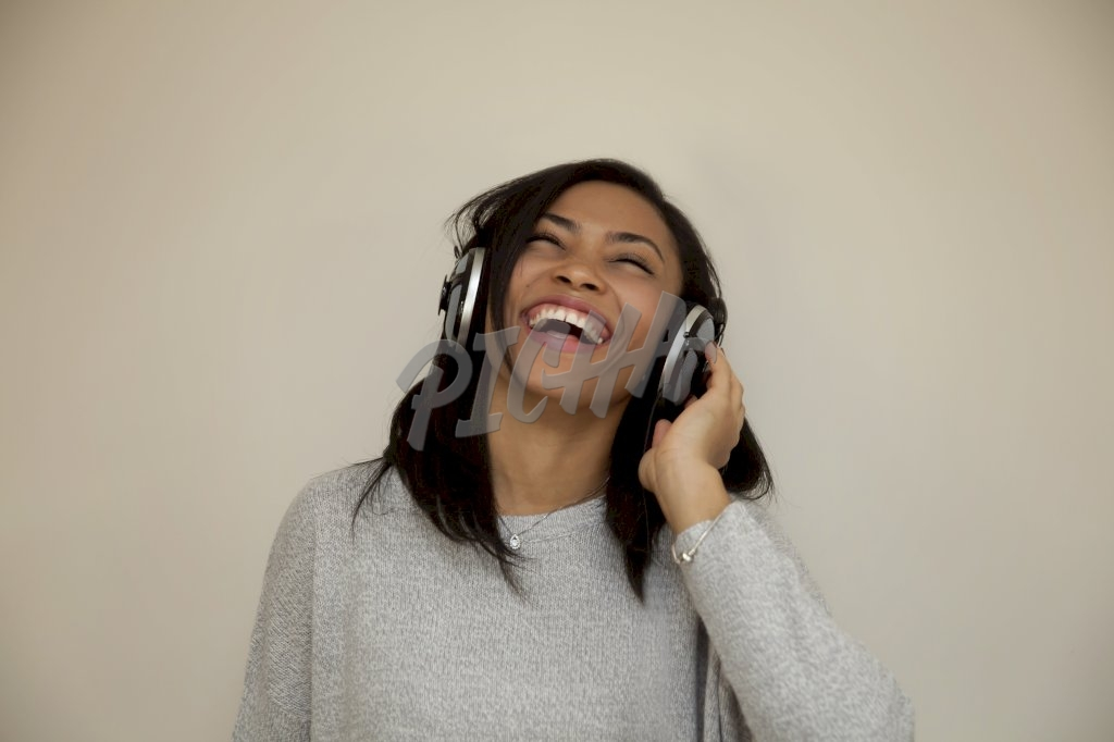 woman laughing while listening to music