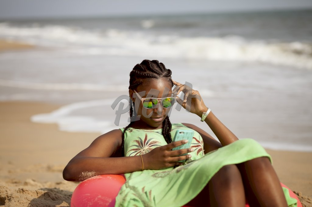 Young woman looking at phone by the beach