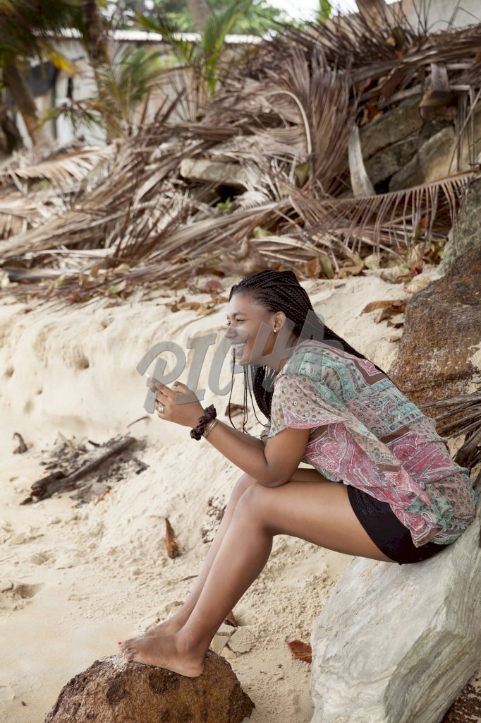 Young woman smiling with her phone on her hand at the beach