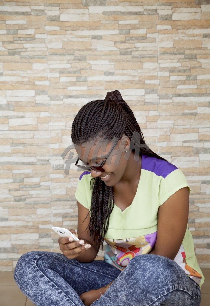 Young woman smiling with her phone on her hand