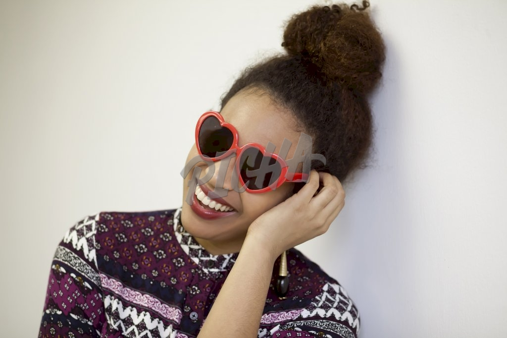 Woman smiling with red heart shape glasses