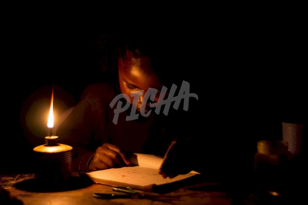 Young girl studying with a lamp