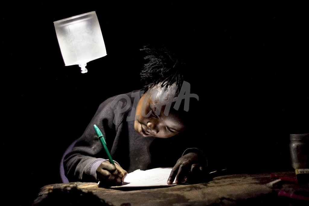 Young girl studying under a lamp