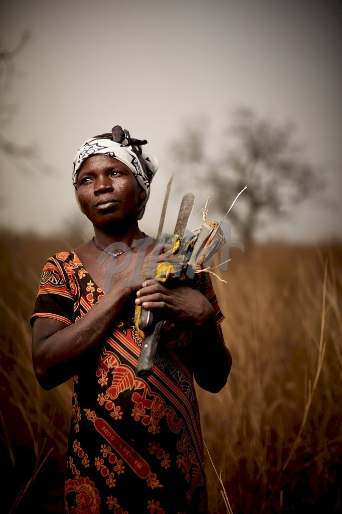 Woman carrying tools in Ghana