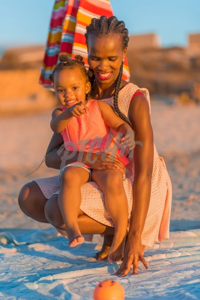 Mother holding little girl at the beach