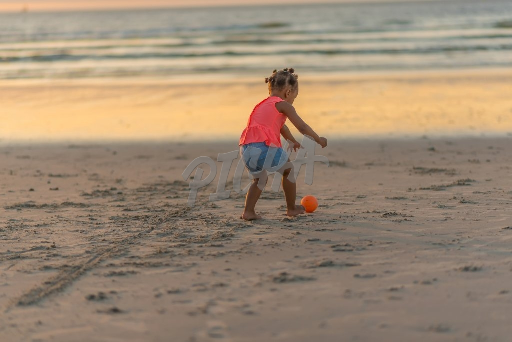 Little girl playing with ball at the beach, South Africa
