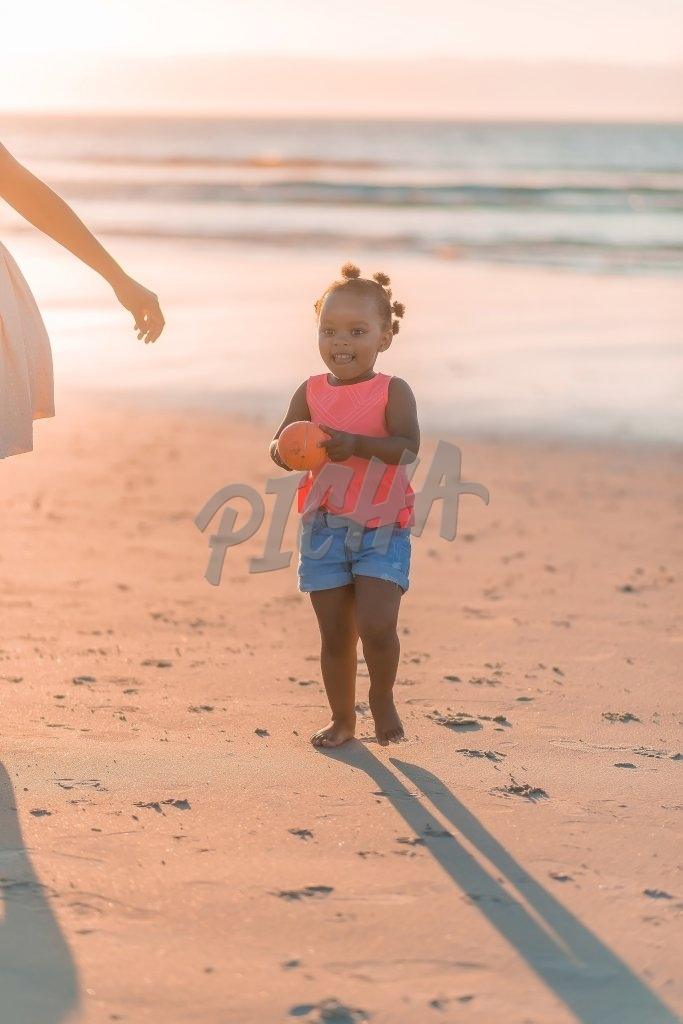 Little girl holding a ball at the beach, South Africa