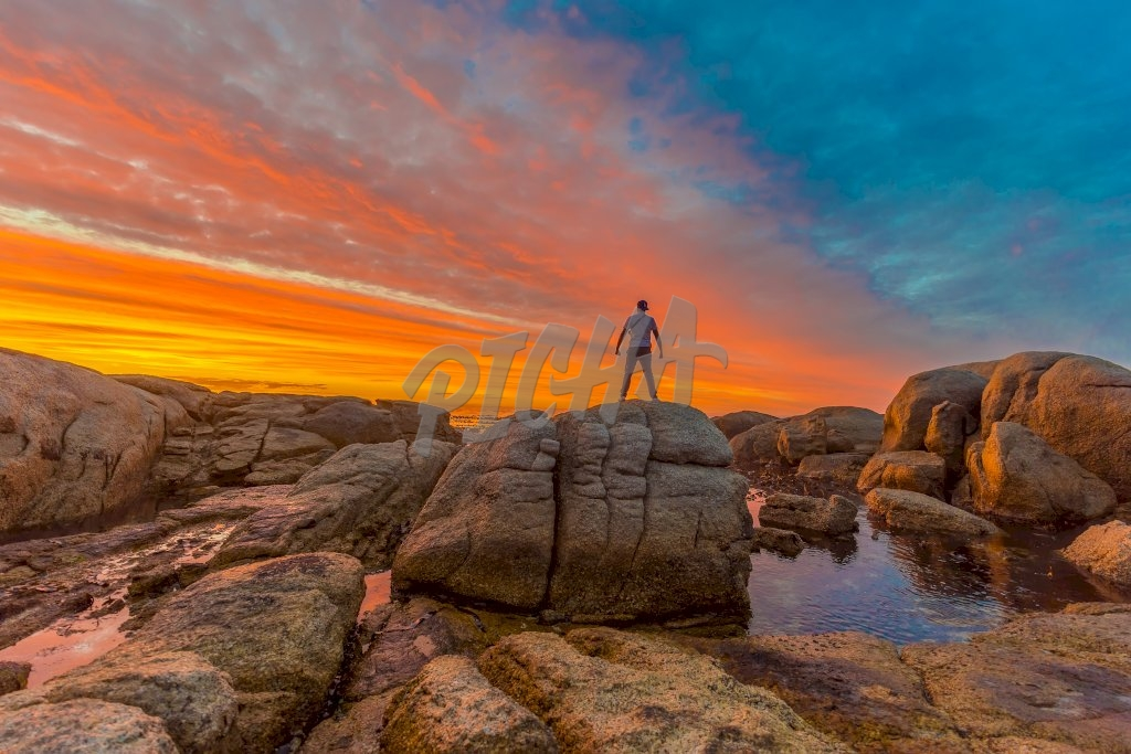 Man standing at sunset by the sea, South africa