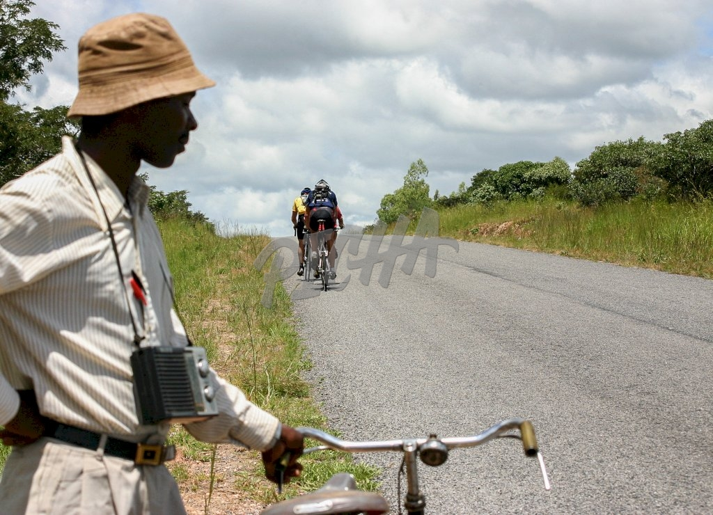Man in Malawi with radio as cyclists ride away