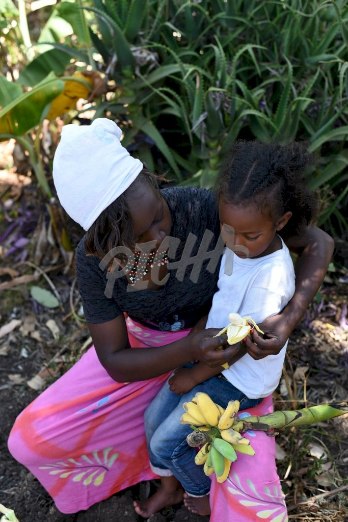 Mother feeding banana to her child