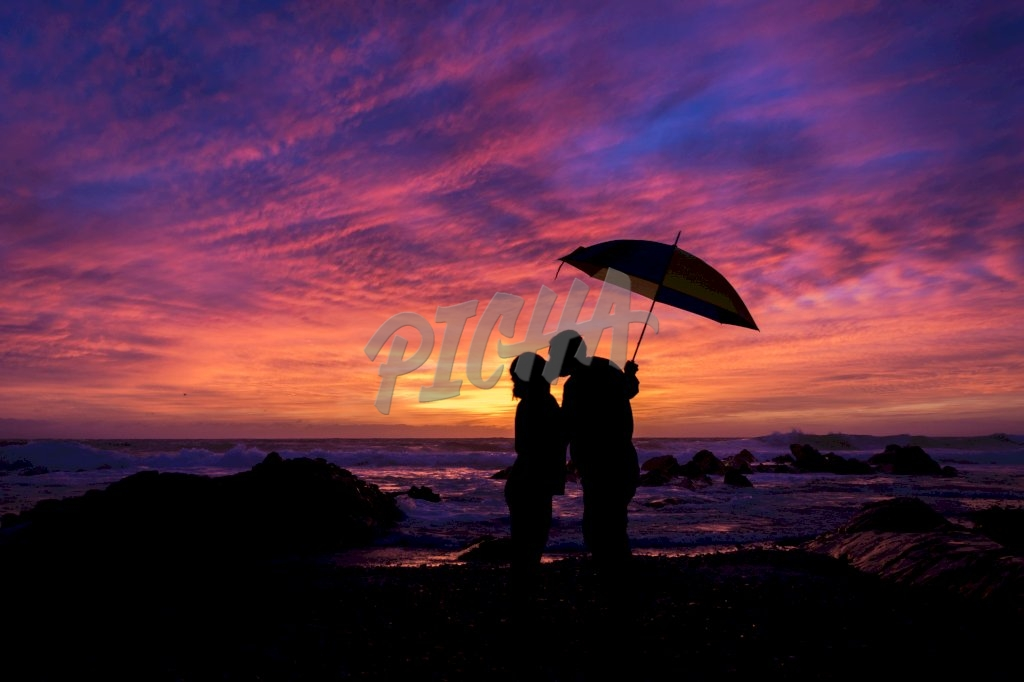 Silhouette couple under an umbrella