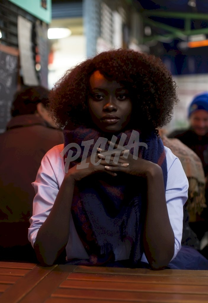 Sudanese woman sitting in a restaurant in France