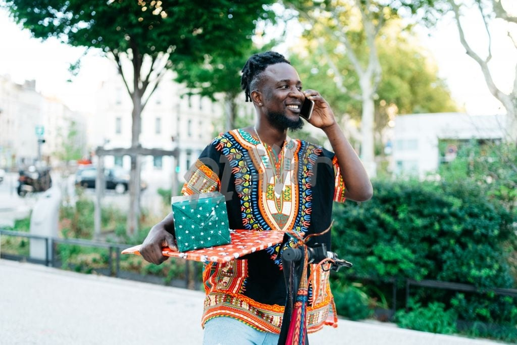 Man carrying gifts while on the phone
