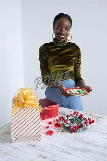 Woman holding a plate of Christmas cookies