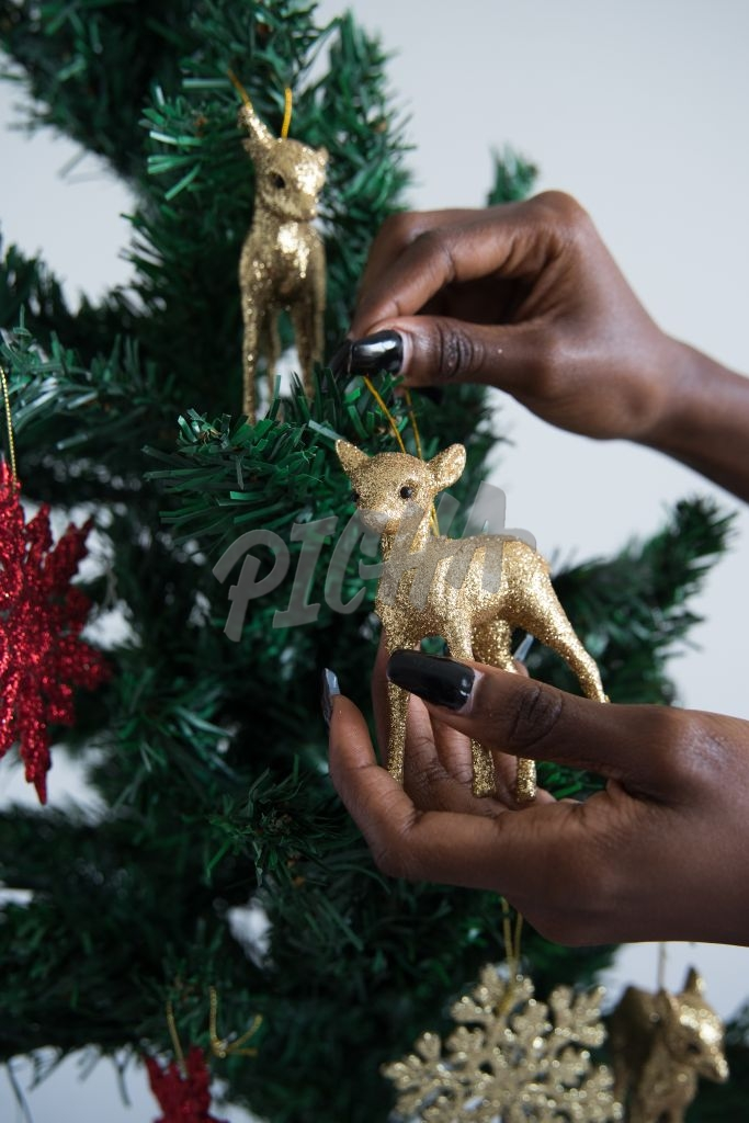 Adding an ornament to the Christmas tree,