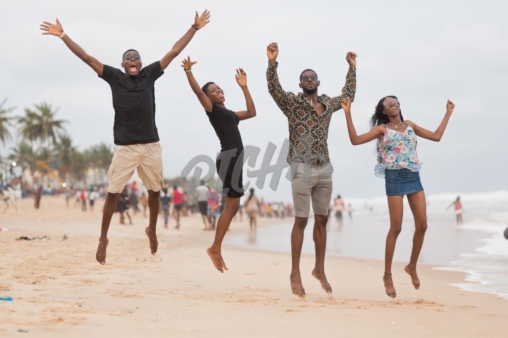 Four friends take a mid air shot at the beach
