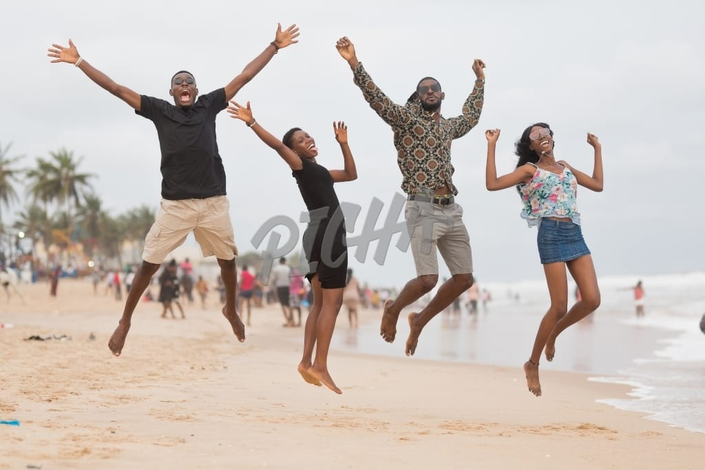 Four friends take a mid air photograph at the beach