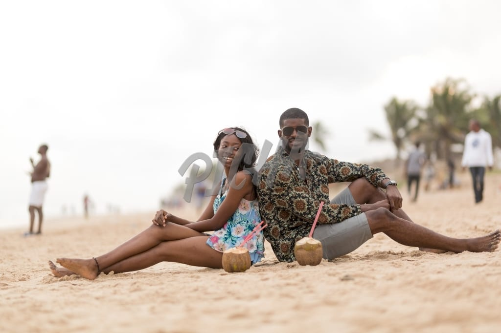 Barefoot young man and woman sit back to back on a sandy beach