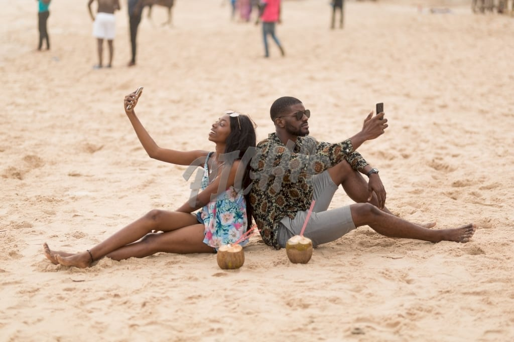 Man and woman take a selfie while seated on sandy beach
