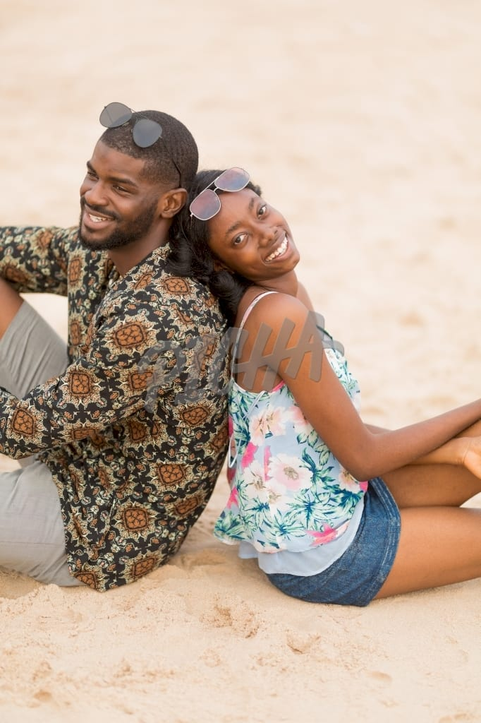 Both man and woman smile while sitting back to back on the sand