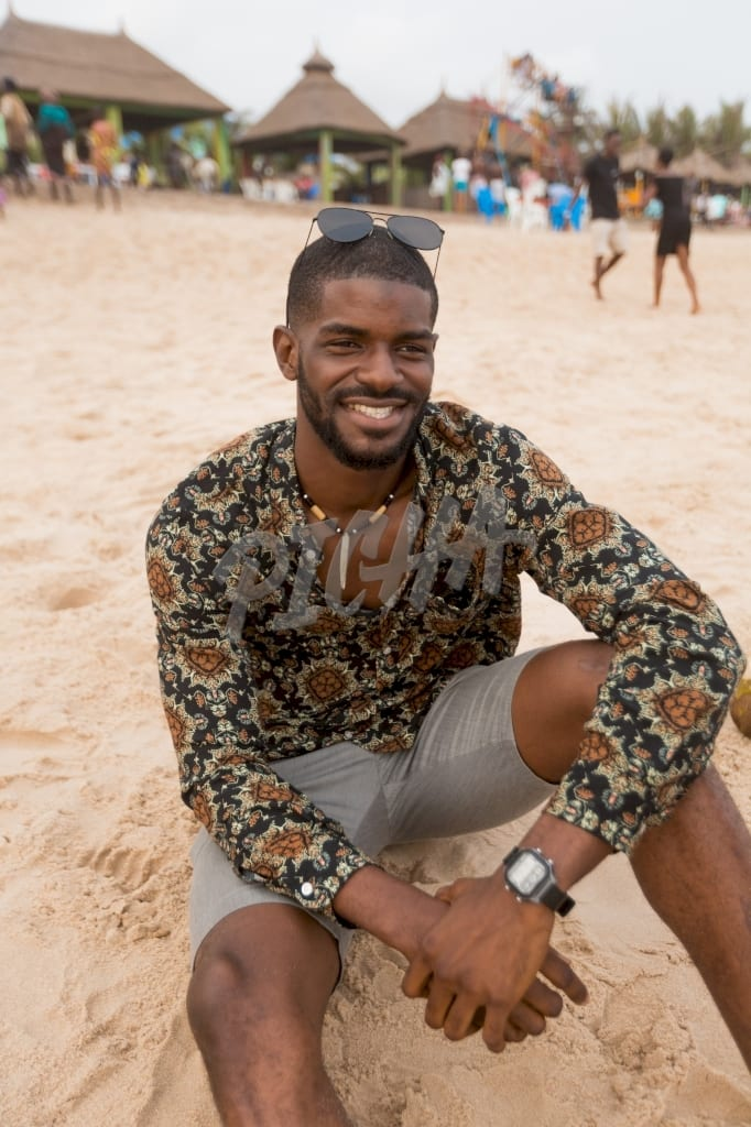 Man gazes with a smile while seated on a sandy beach