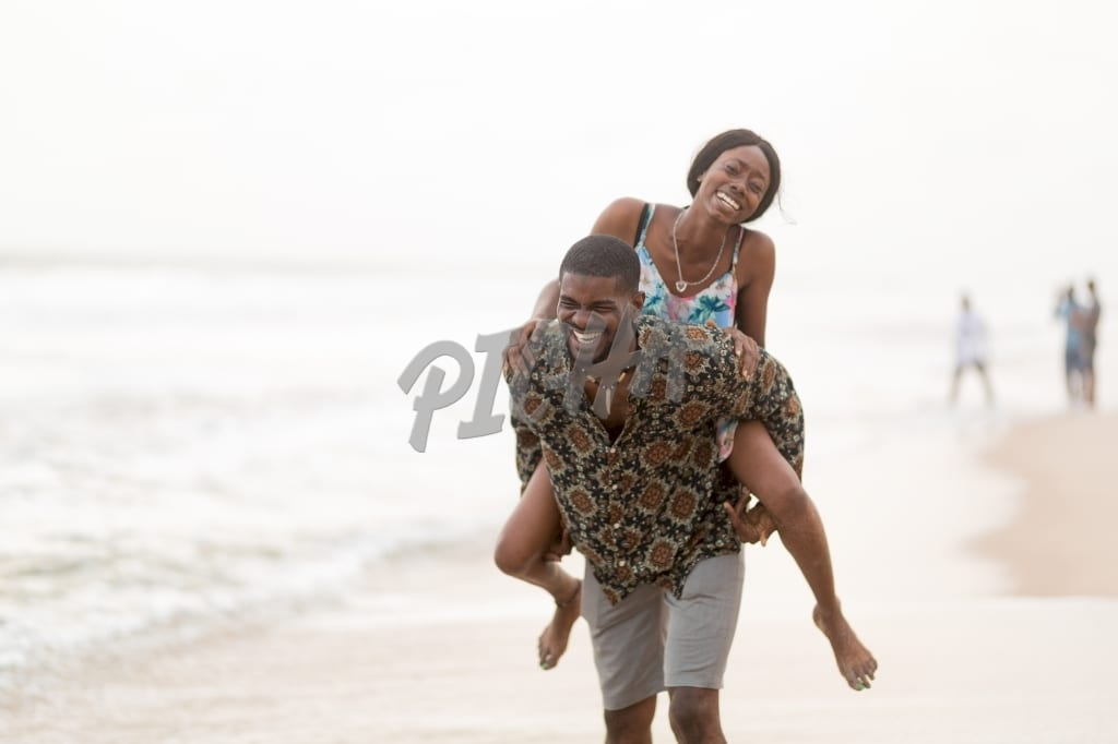 Man carries lady on back while at the beach