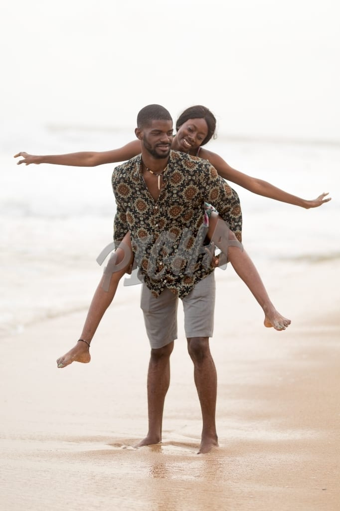 couple has fun playing piggy back at the beach