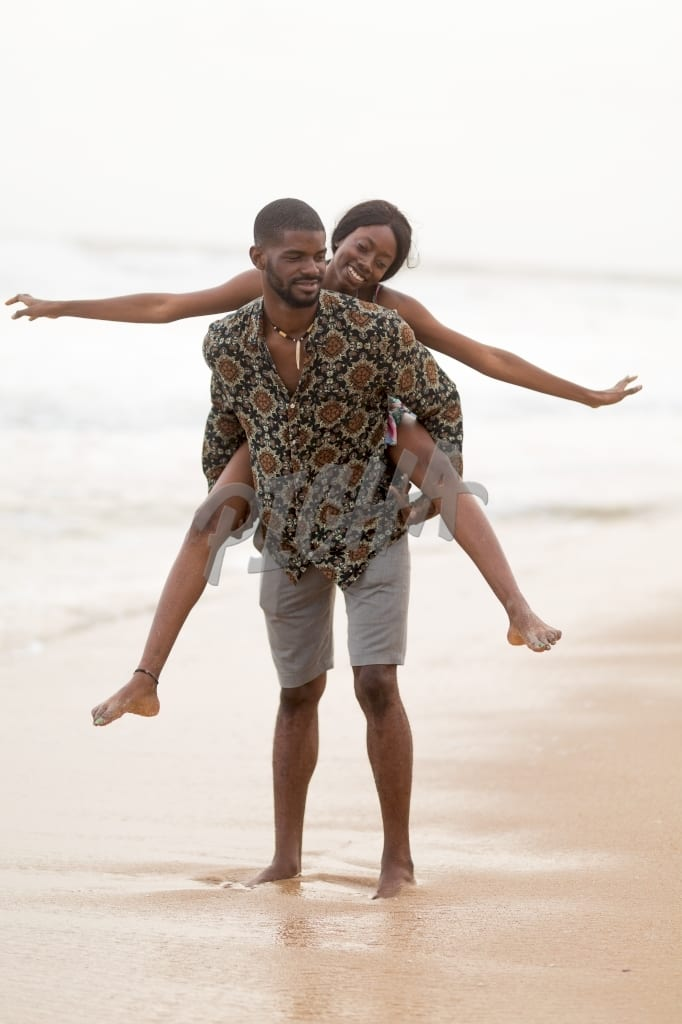 Couple have a good time playing piggy back on the beach