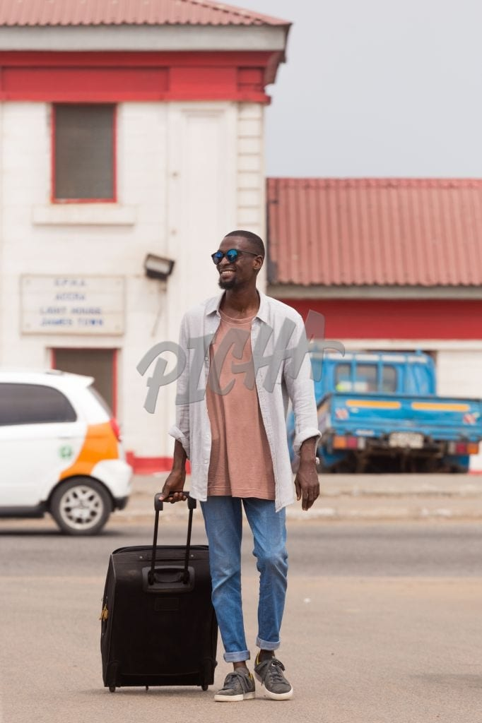 Man pulling a suitcase in Accra