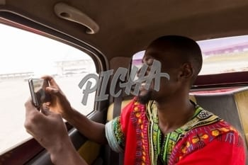 Man taking a photo of Accra from a car