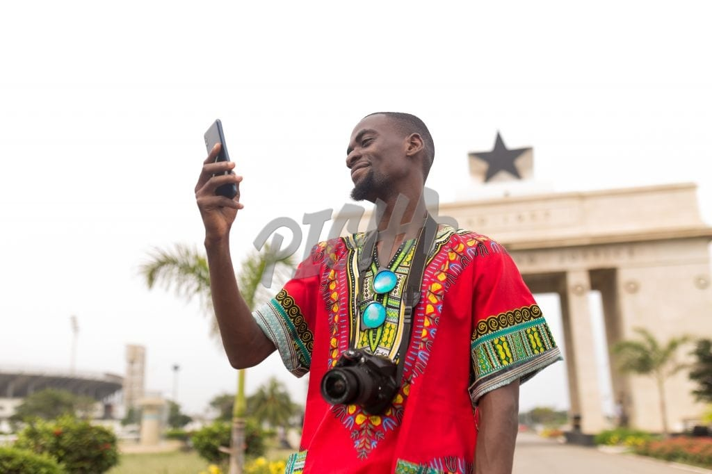 Man checking phone at independence arch in Accra