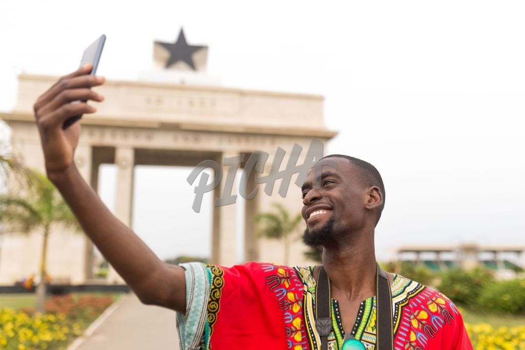 Man taking a selfie at the independence arch in Accra