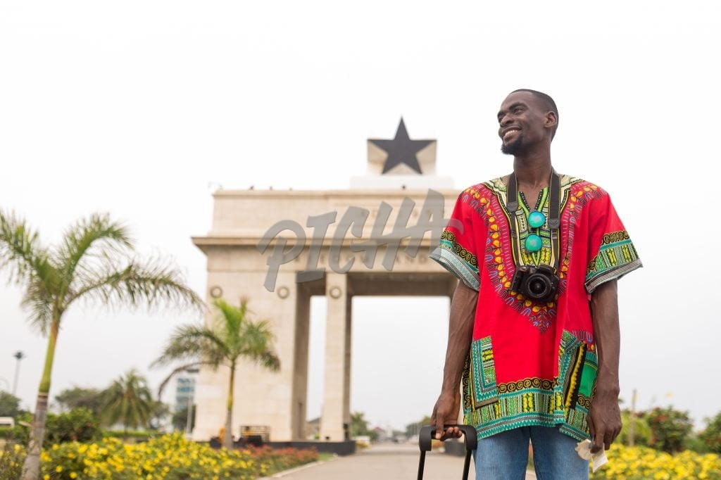 Man standing by the independence arch in Accra