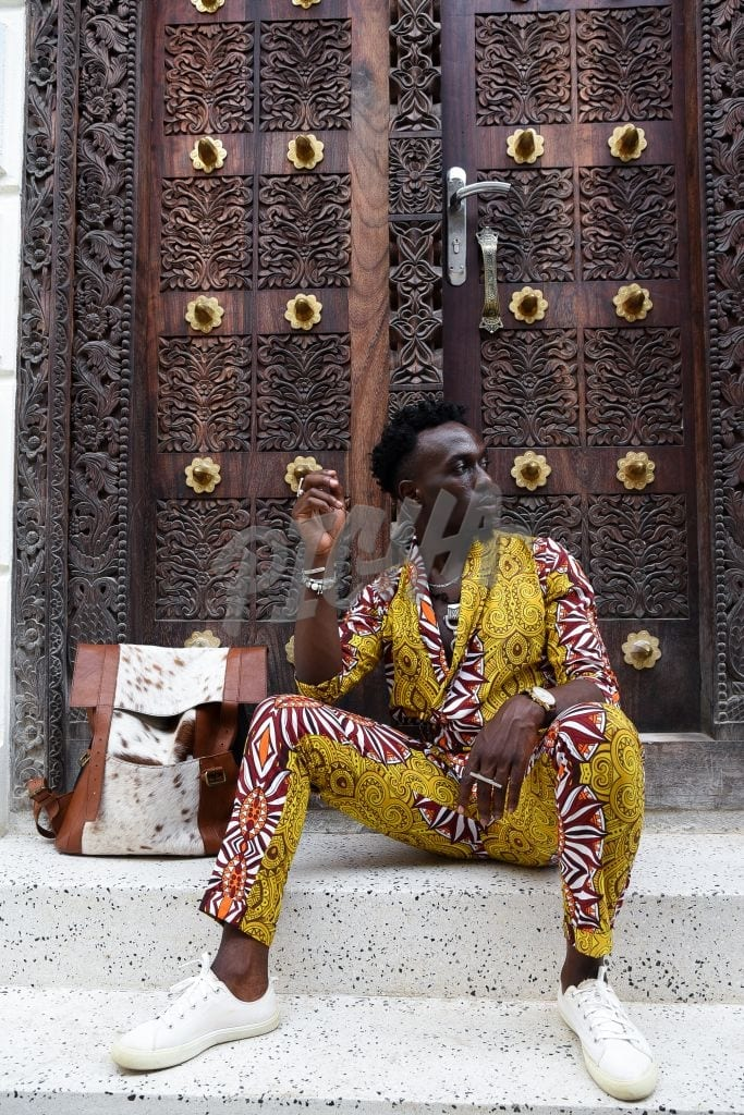 Stylish man sitting by a carved door