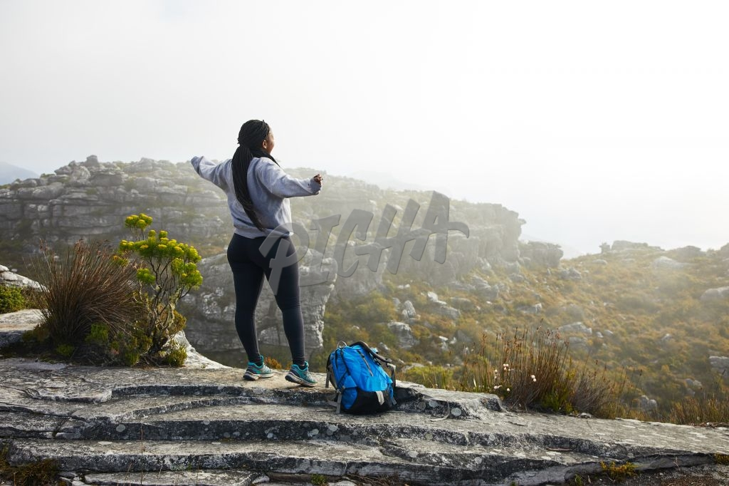 Woman celebrating on edge of mountain