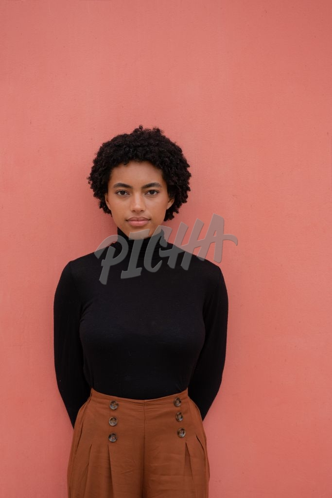 Young woman with curly hair against colorful background