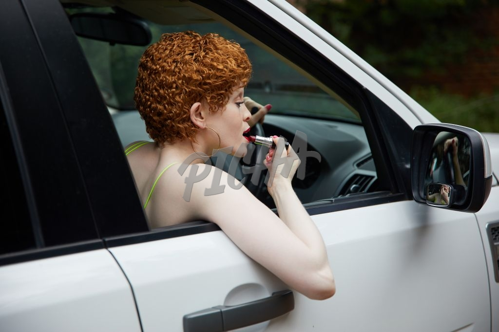 Putting on lipstick in the car